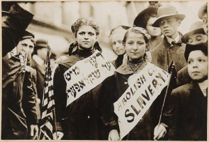 """Jewish girls in the 1909 International Workers' Day parade in New York City; draped over their chests are signs reading ""Abolish child slavery!"" in both English and Yiddish.""  ("